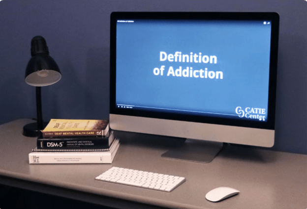 "Photo of a desk with some books, a lamp, and an iMac computer showing ""Definition of Addiction"" in white text on a blue screen."